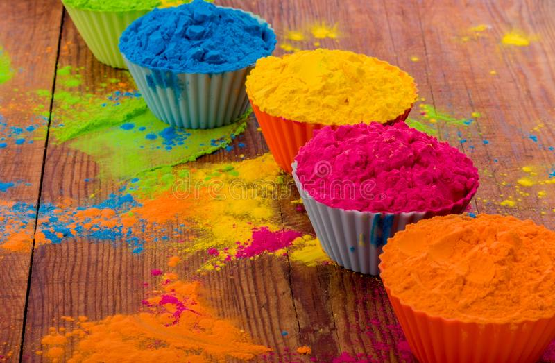 Colorful Holi powder in cups closeup. Bright colours for Indian holi festival in circle of clay pots. Selective focus royalty free stock image