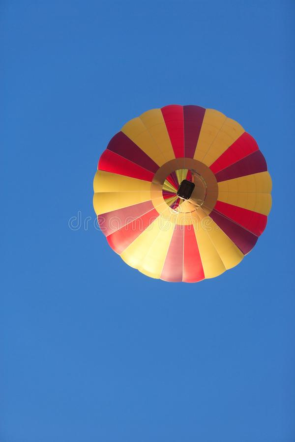 A colorful hot air balloon against a blue sky. stock image