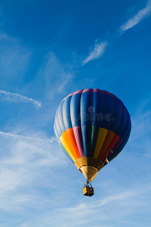 Colorful hot air balloon in blue sky. At sunset royalty free stock image