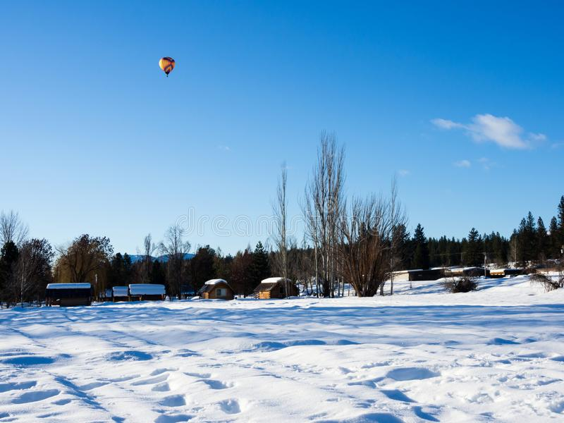 Colorful hot air balloon flying above a snow covered field royalty free stock photography