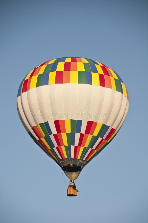 Colorful hot air balloon flying against the blue morning sky. Colorful hot air balloon flying  the blue morning sky stock photo