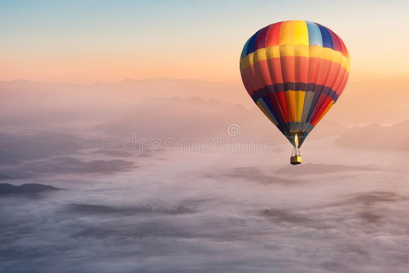 Colorful hot air balloon flying in the air with fog and scenery mountains royalty free stock image