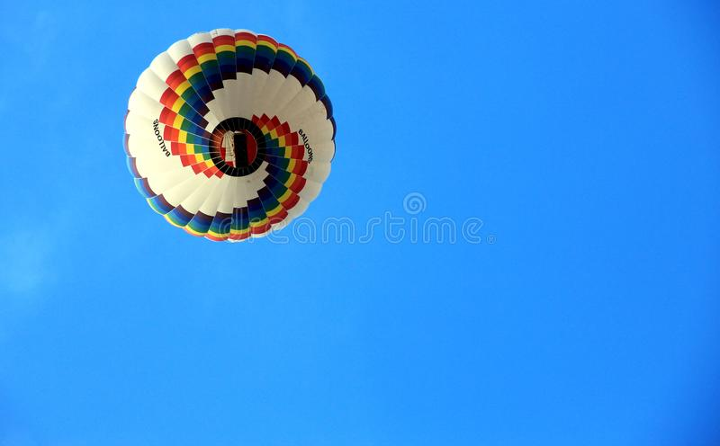 A colorful hot air balloon flying in the large blue sky. stock photos