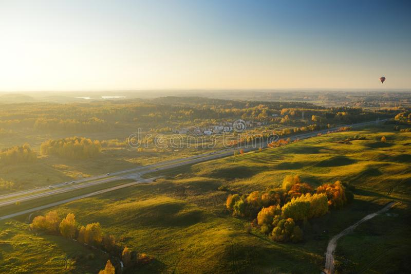 Colorful hot air balloon flying over fields surrounding Vilnius city on sunny autumn evening. stock photo