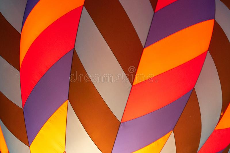 Close up of a Hot air ballon while it is being blown up. A colorful hot air balloon while on the ground being blown up stock images