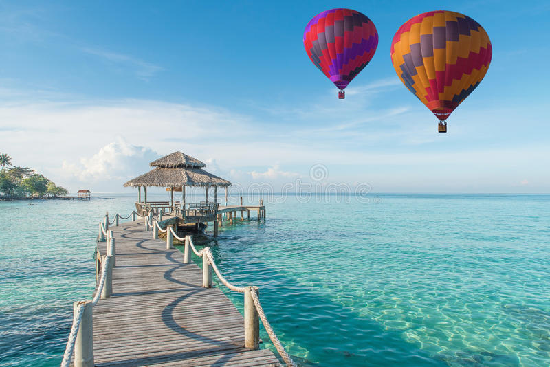 Colorful hot air balloon over Phuket beach with blue sky background, Phuket, Thailand Tropical hut and wooden bridge at holiday r. Esort. Summer travel in Phuket royalty free stock image