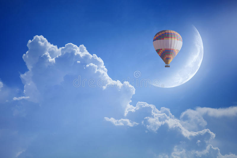 Colorful hot air balloon rise up into blue sky above white cloud. Idyllic heavenly background - colorful hot air balloon rise up into blue sky above white clouds stock photo