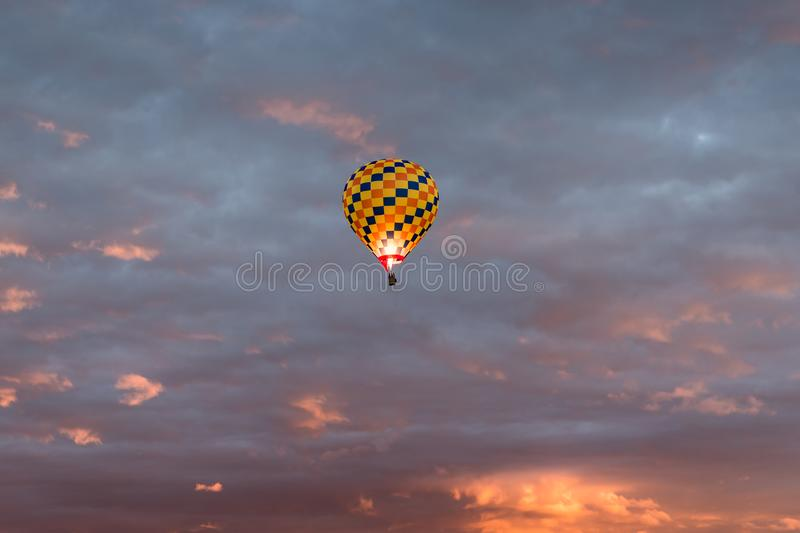 Colorful hot air balloon in yellow, orange, and dark blue colors glowing against a dramatic colorful sky and clouds at sunrise royalty free stock photos