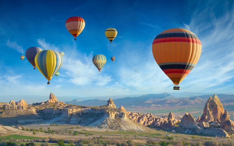 Colorful hot air balloons fly in blue sky over amazing valleys with fairy chimneys in Cappadocia, Turkey stock photography