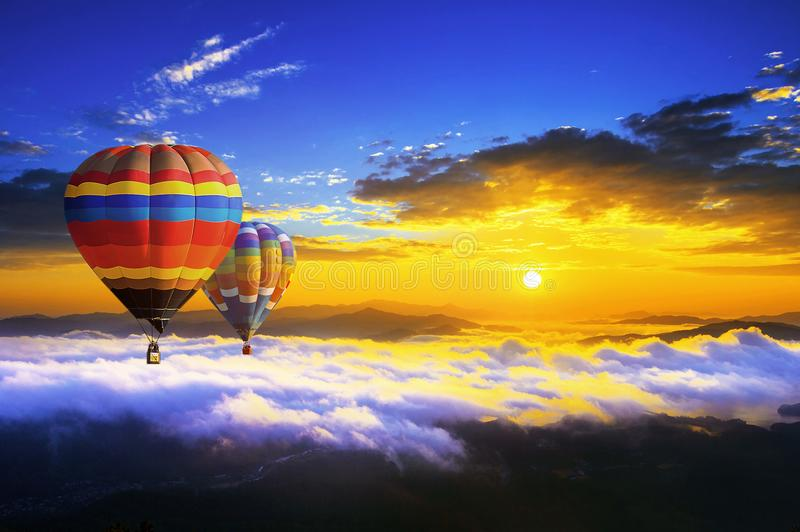 Colorful hot air balloons flying over the mountain covered by morning fog at sunrise royalty free stock photo