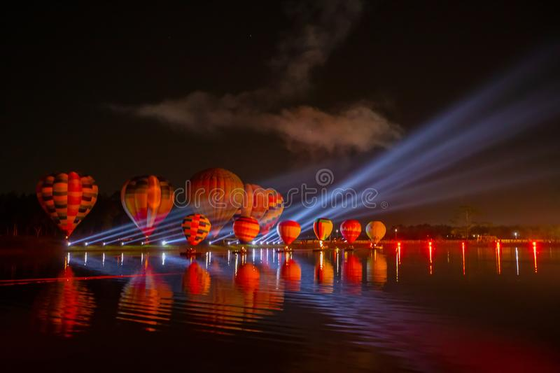 Colorful hot air balloons flying over river on night festival stock photography