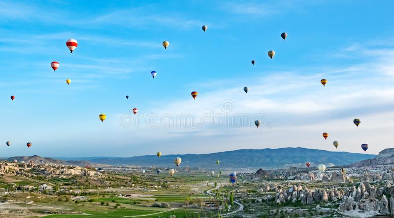 Colorful hot air balloons flying over rock landscape at Cappadocia Turkey royalty free stock photography