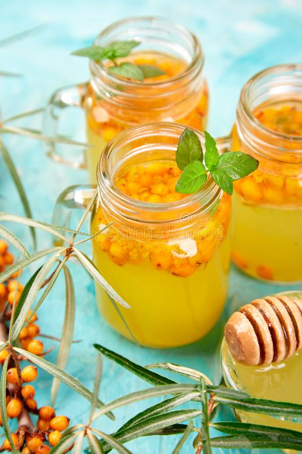 Colorful hot sea buckthorn tea with ginger and honey. And sea buckthorn berries on blue table. Top view. Vitaminic healthy stock photography