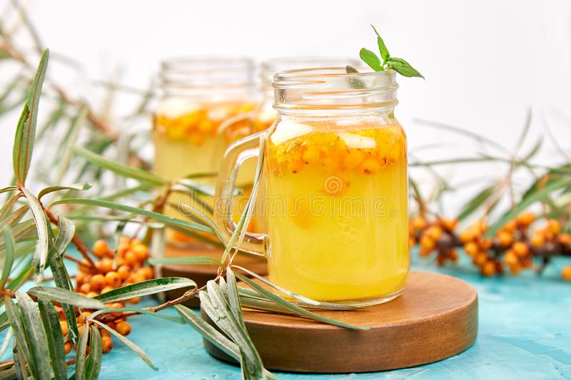 Colorful hot sea buckthorn tea with ginger and honey. And sea buckthorn berries on blue table. Top view. Vitaminic healthy royalty free stock photo