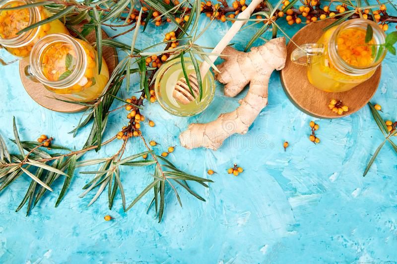 Colorful hot sea buckthorn tea with ginger and honey. And sea buckthorn berries on blue table. Top view. Vitaminic healthy royalty free stock photos