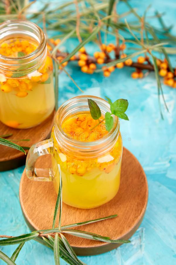Colorful hot sea buckthorn tea with ginger and honey. And sea buckthorn berries on blue table. Top view. Vitaminic healthy royalty free stock images