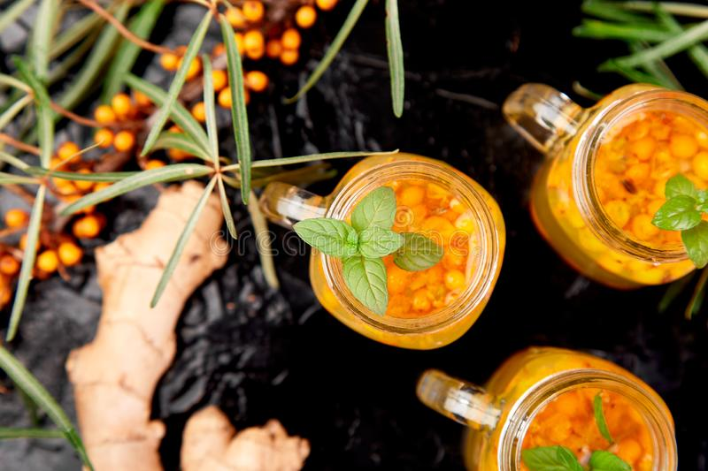 Colorful hot sea buckthorn tea with ginger and honey. Vitaminic healthy sea buckthorn tea in small glass cups with fresh raw sea buckthorn berries, honey on stock image