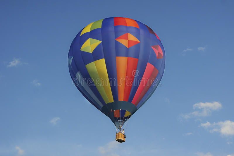 Colorful hotair balloon with blue sky. Balloon with red, blue, yellow and orange colors in diamond and rectangle shapes. Blue sky with some white clouds. Taken royalty free stock image