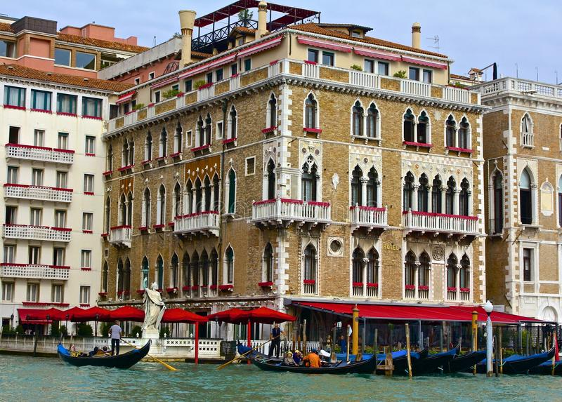 Colorful Hotel and Gondolas Along the Grand Canal. A stately hotel rises above tourists in gondolas on the Grand Canal in Venice, Italy stock photos