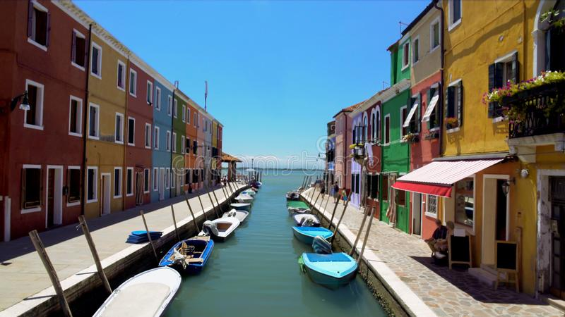 Colorful houses and boats moored along canal on Burano island, locals in street royalty free stock image