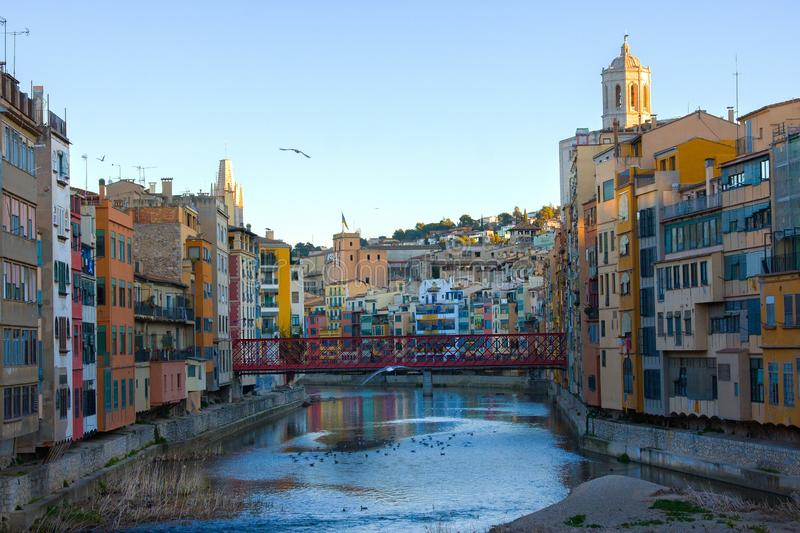 Colorful and houses and bridge Pont de Sant Agusti reflected in river Onyar, in Girona, Catalonia, Spain. Church of Sant Feliu and royalty free stock photos