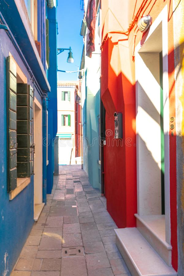 Colorful houses of Burano Island. Venice. Typical street with hanging laundry at facades of colorful houses royalty free stock image
