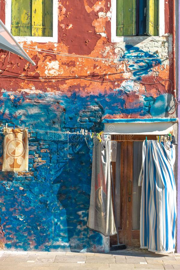 Colorful houses of Burano Island. Venice. Typical street with hanging laundry at facades of colorful houses royalty free stock photo