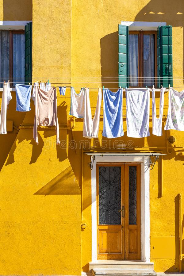 Colorful houses of Burano Island. Venice. Typical street with hanging laundry at facades of colorful houses stock images
