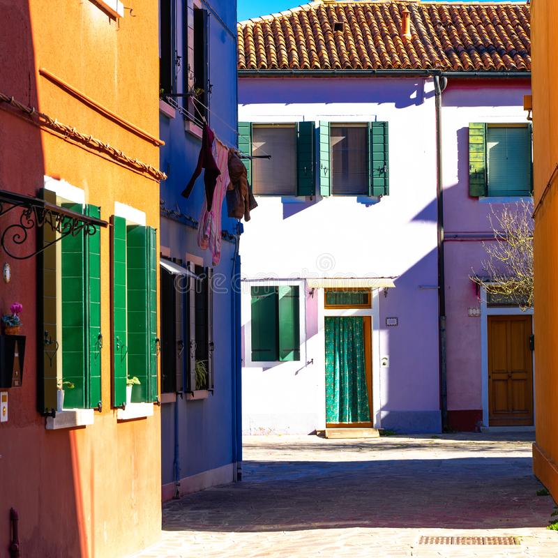 Colorful houses of Burano Island. Venice. Typical street with hanging laundry at facades of colorful houses stock image