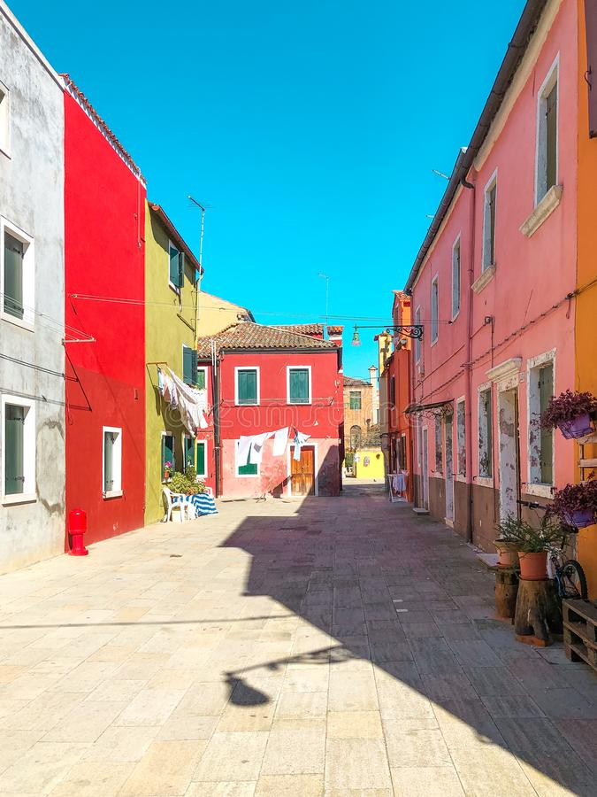Colorful houses of Burano Island. Venice. Typical street with hanging laundry at facades of colorful houses stock photos