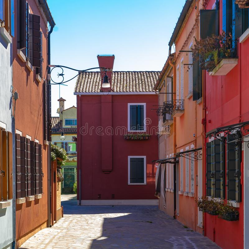 Colorful houses of Burano Island. Venice. Typical street with hanging laundry at facades of colorful houses stock photo