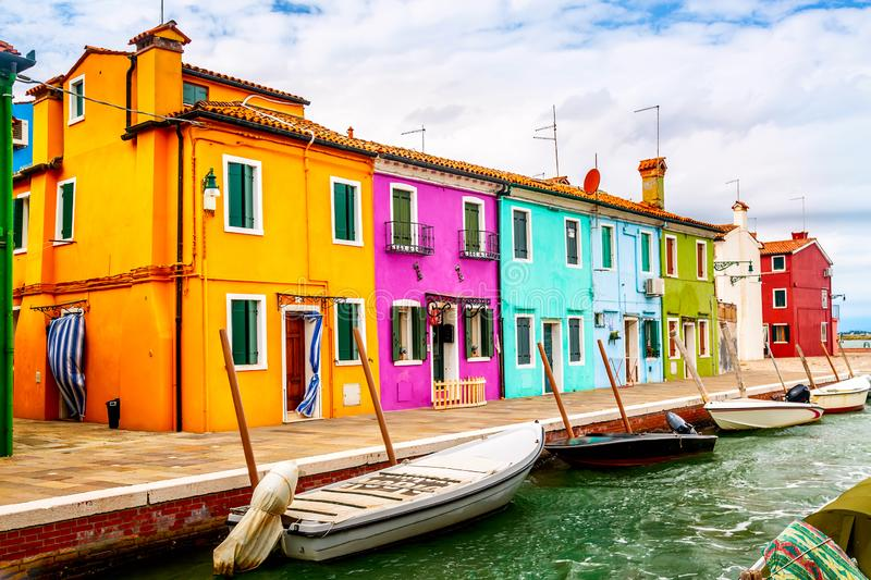 Colorful houses in Burano near Venice, Italy with boats and beautiful blue sky in summer. Famous tourist attraction in Venice stock photography