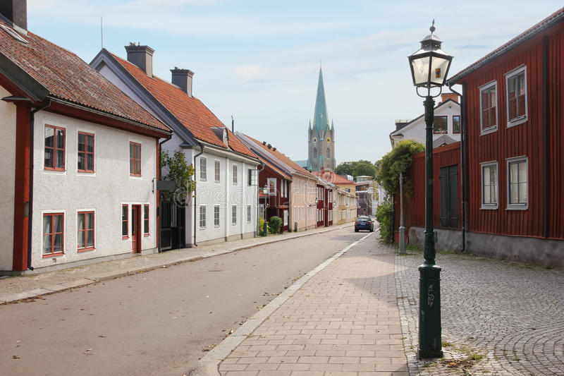 Colorful houses and cathedral. Linkoping. Sweden. A typical street flanked by new and old colorful wooden houses and cathedral tower at a distance. Linkoping stock images