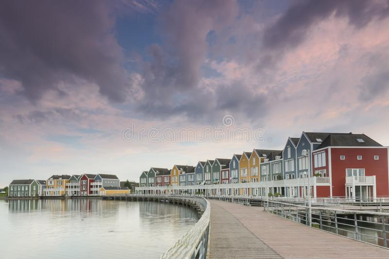 Colorful houses at dusk in Houten, The Netherlands. Row of Colorful houses in Houten, Netherlands, at dusk with reflections on Rietplas lake under a dark cloudy stock photos