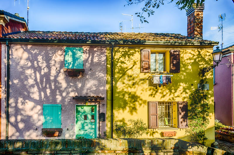Colorful houses in Italy. Group of colorful houses in the old square with masonry tanks originally used for the preservation of freshly caught fish in Italy royalty free stock images