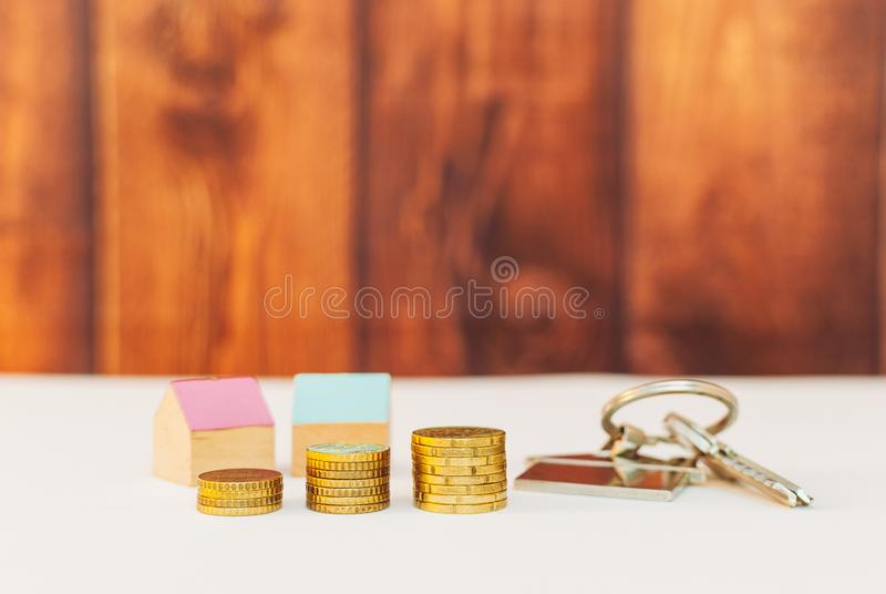 Colorful houses with stack coins. Miniature colorful houses with stack coins on a wooden background using as property and business concept, money, finance stock photography