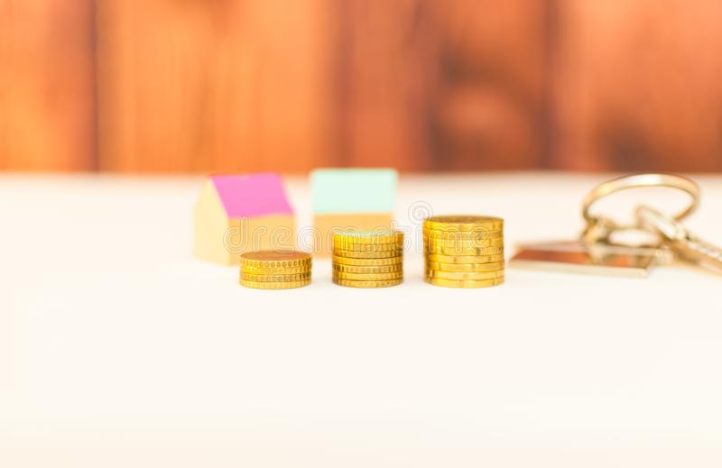 Colorful houses with stack coins. Miniature colorful houses with stack coins on a wooden background using as property and business concept, money, finance stock photo