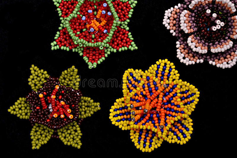 Colorful huichol flowers. Colorful mexican craftwork created by huichol people in Jalisco, Mexico.Tiny beads are handwoven to create their sacred flower royalty free stock images