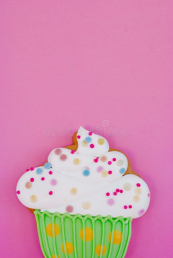 Colorful icing cookie in cupcake shape on pink background royalty free stock photos