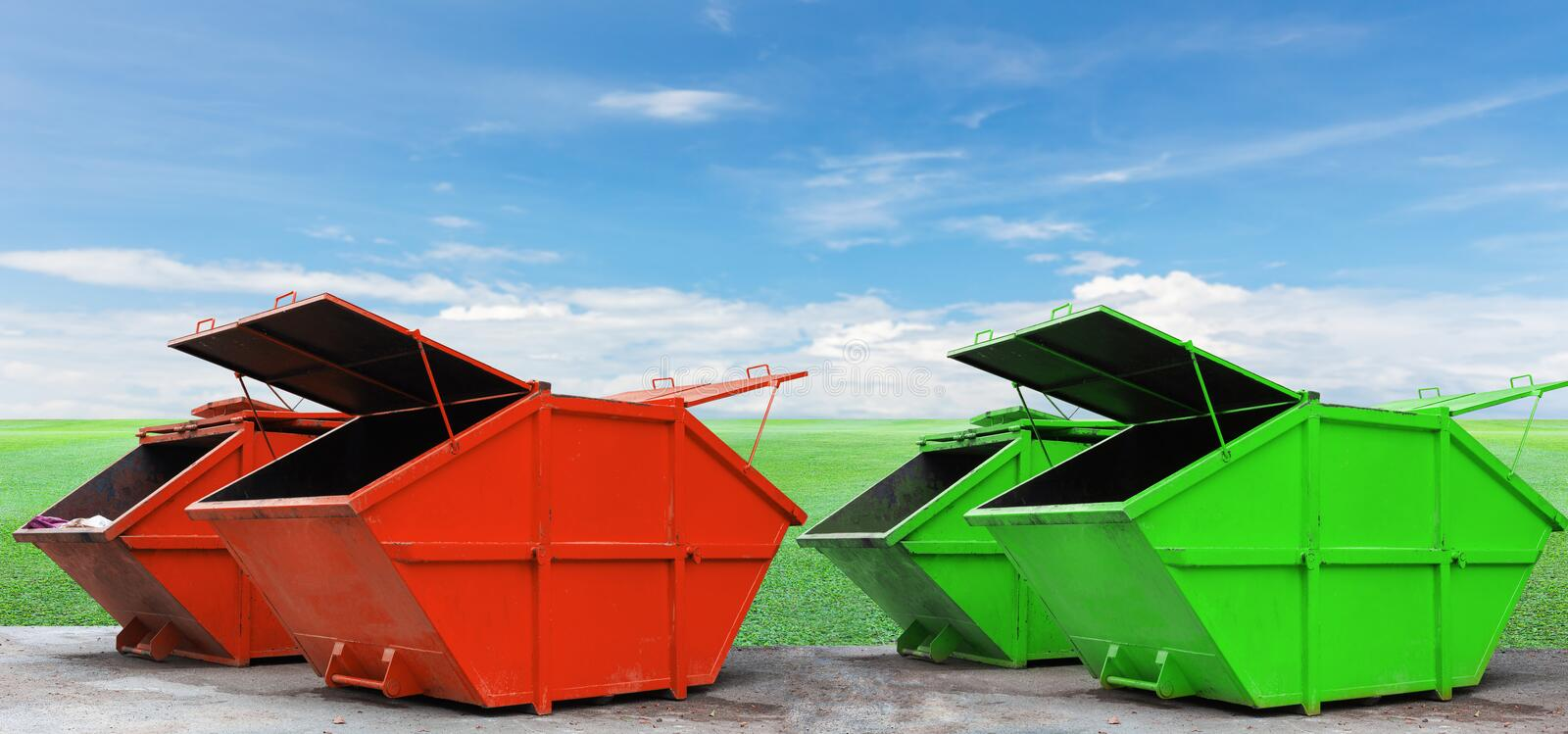 Colorful Industrial Waste Bin dumpster for municipal waste or. Industrial waste on green grass and blue sky background,with ecology concept stock image