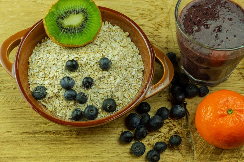 Colorful ingredients for breakfast or smoothie with berries, kiwi, oatmeal and oranges on a wood background royalty free stock photography