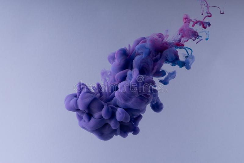 Colorful Ink swirling in water. Cloud of silky ink on white background royalty free stock photo