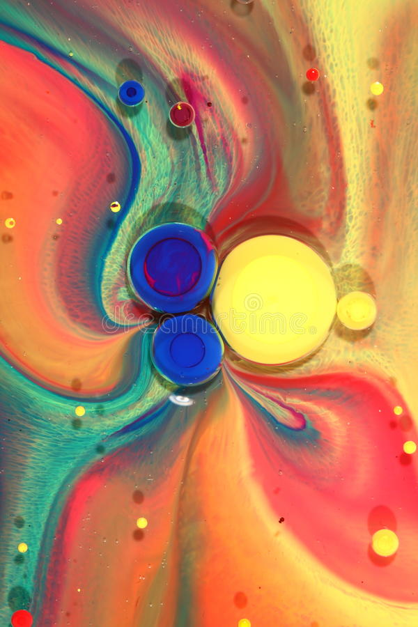 Colorful ink swirls on oil stock image