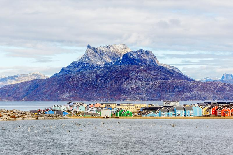 Colorful Inuit buildings in residential district of Nuuk city with lake in the foreground and snow peak of Sermitsiaq mountain, royalty free stock photo