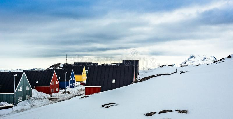 Colorful inuit houses along the street covered in snow, at the f stock images