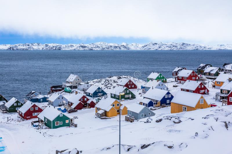Colorful inuit houses among rocks and snow at the fjord in a sub. Urb of arctic capital Nuuk, Greenland stock photo