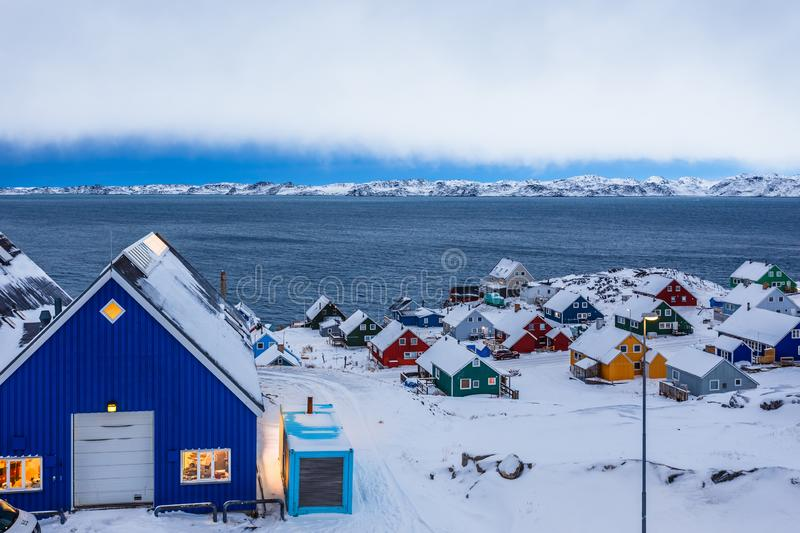 Colorful inuit huts among rocks and snow at the fjord in a suburb of arctic capital Nuuk, Greenland. Colorful inuit huts among rocks and snow at the fjord in a stock photos