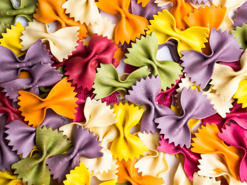 colorful Italian pasta background. Various colors of bow tie farfalle pasta. Top view stock photography