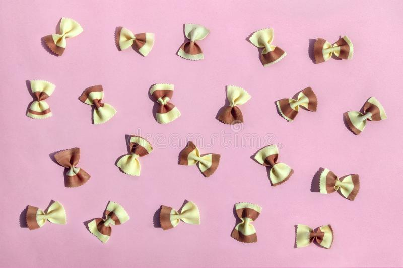 Colorful Italian pasta bows on pink background. Dry pasta for cooking healthy food, top view, flat lay royalty free stock image
