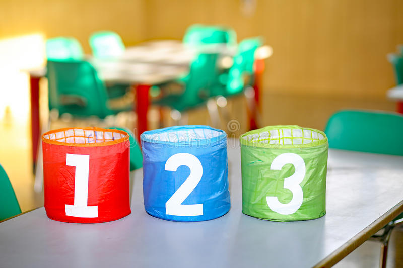 Colorful jars with one two and three numbers. In a classroom of a school stock images